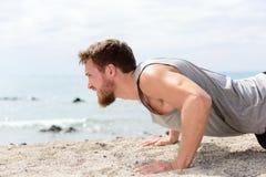 Konditionman som gör liggande armhävningövning på stranden Arkivfoton