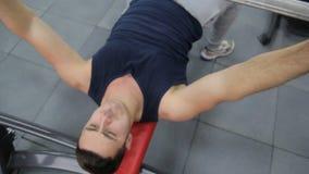 Konditionmannen i idrottshallutbildningsbröstkorg tränga sig in göra press för den plana bänken med skivstången lager videofilmer