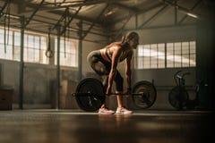 Konditionmodell som utför övning för lyfta för vikt på idrottshallen royaltyfria foton