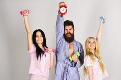 Konditionmorgonbegrepp Gladlynta vänner med hantlar i inhemsk kläder, grå bakgrund Skäggigt manhålllarm royaltyfri fotografi