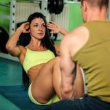 Konditionpargenomkörare - den färdiga mannen och kvinnan utbildar i idrottshall Royaltyfria Foton