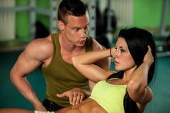Konditionpargenomkörare - den färdiga mannen och kvinnan utbildar i idrottshall Royaltyfri Bild