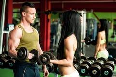Konditionpargenomkörare - färdiga mann och kvinnan utbildar i idrottshall arkivbild