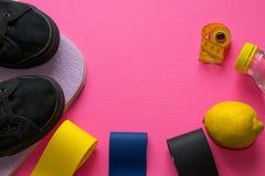 Konditionsammansättning av färgrika elastiska gummiexpanders, ny citronjuice som mäter bandet, svarta gymnastikskor på rosa bakgr arkivbild