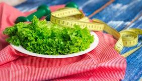Konditionsammansättning av grön grönsallat på plattan, vikter och linjal Arkivfoto