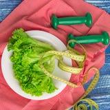 Konditionsammansättning av grön grönsallat, vikter och linjalen Royaltyfria Foton