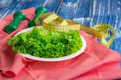 Konditionsammansättning av grönsallat på plattan, vikter och linjal Royaltyfria Bilder