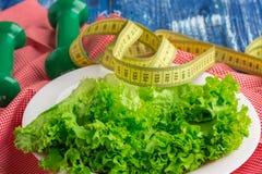 Konditionsammansättning av grönsallat, vikter och linjalen Royaltyfri Foto