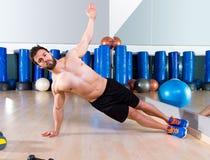Konditionsidan skjuter ups manliggande armhävning på idrottshallen Arkivbilder