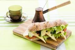 Konditionsmörgås med avokadot och ost och svart kaffe Arkivfoto