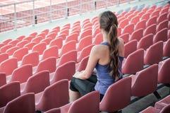 Konditionsportkvinnan i modesportswear, sitter se körande sportflickor, konditionövning i stadsgatan arkivfoton