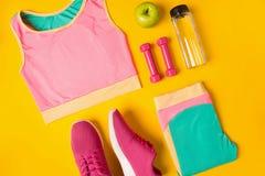 Konditiontillbehör på gul bakgrund Gymnastikskor, flaska av vatten, hantlar och sportöverkant arkivbilder