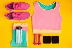 Konditiontillbehör på gul bakgrund Gymnastikskor, flaska av vatten, hantlar och sportöverkant royaltyfri fotografi