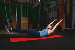 Konditionung flicka i idrottshallen som gör övningar med abdominals Crossfit Arkivfoton