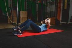 Konditionung flicka i idrottshallen som gör övningar med abdominals Crossfit Royaltyfria Bilder