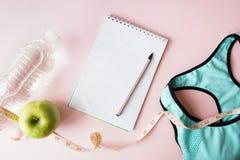 Konditionutrustning med midjamätning, behå och det gröna äpplet och anteckningsboken för övning på rosa bakgrund Anteckningsbokut royaltyfria bilder