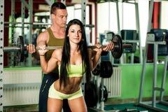 Konditionyouplegenomkörare - färdiga mann och kvinnan utbildar i idrottshall royaltyfria bilder