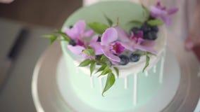 Konditor dekorerar trevligt den ljusbruna kakan för turkosbröllop med blåbär