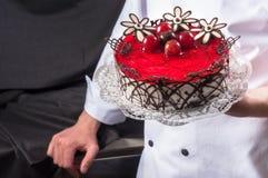 Konditor, der köstlichen Kuchen anhält lizenzfreie stockbilder