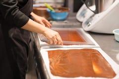 Konditor macht Schokoladennachtisch am Süßwarengeschäft stockbild