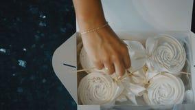Konditor sätter marängen i en ask på en pinne med en försiktig pilbåge arkivfilmer