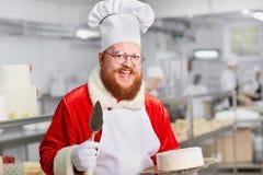 Konditor Santa Claus mit einem Kuchen in seinen Händen für Weihnachten Lizenzfreie Stockfotografie