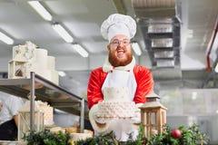 Konditor Santa Claus mit einem Kuchen in seinen Händen für Weihnachten Stockfoto