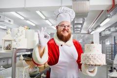 Konditor Santa Claus mit einem Kuchen in seinen Händen für Weihnachten Stockfotos