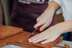 Konditor schneidet die Schicht des Kuchens Stockbild