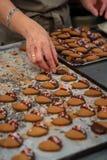 Konditor som gör kakor, tedegar som doppas i choklad och dekoreras med sockerhjärtor arkivfoton