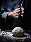 Konditorhand som strilar vitt mjöl över rå deg på kitche royaltyfri fotografi