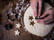 Konditorhandbruk som klipper formen för att klippa kakadeg på kök arkivbilder