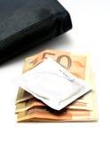 Kondom mit Geld Stockfotos