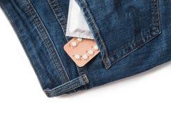 Kondomar i packe i jeans begreppssafen könsbestämmer Sjukvårdmedicin, det att använda preventivmedel och födelsekontroll arkivbilder