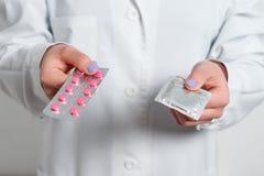 Kondomar och preventivmedel i händerna av en doktor för säkert könsbestämmer royaltyfri bild