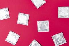 Kondomar på rosa bakgrund Begreppet av det att använda preventivmedel och säkra könsbestämmer Skydd från HIV under samlag Royaltyfria Bilder