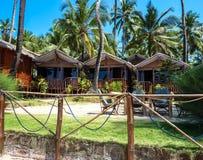 Kondygnacja drewniani bungalowy na tle kokosowe palmy jaskrawego niebieskie niebo, Palolem plaża obrazy stock