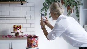 Konfektblogg Kvinna i den vita skjortan som fotograferar kakan som dekoreras med blommor Konditor dekorerade kakan och stock video
