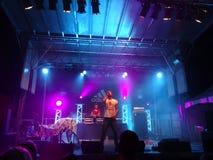 konferenciéyogin sjunger in i mic, som han preforms på etapp med discjockeyn Drez Royaltyfri Foto