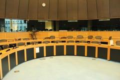 Konferenzrundtisch mit Mikrophonen und Stühlen Stockbild