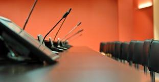 Konferenztisch, Mikrophone und Bürostühle lizenzfreie stockbilder