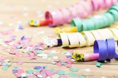 Konfettier, banderoller och partiblåsare på wood bakgrund Royaltyfri Bild