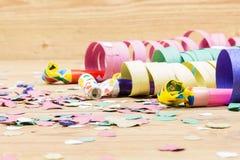Konfettier, banderoller och partiblåsare på wood bakgrund Royaltyfri Fotografi