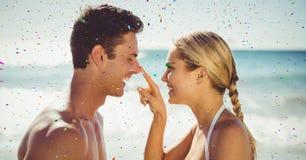 Konfettier mot par på stranden arkivfoton