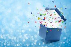 Konfettier som ut poppar från den blåa gåvaasken arkivfoto