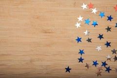 Konfettistjärnor på träbakgrund 4th Juli, självständighetsdagen, kortet, inbjudan i USA sjunker färger Sikten från överkant, tömm Arkivbild