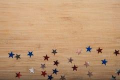 Konfettistjärnor på träbakgrund 4th Juli, självständighetsdagen, kortet, inbjudan i USA sjunker färger Sikten från överkant, tömm Royaltyfri Foto