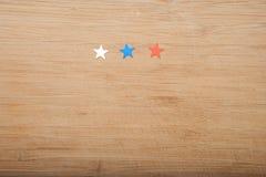 Konfettistjärnor på träbakgrund 4th Juli, självständighetsdagen, kortet, inbjudan i USA sjunker färger Sikten från överkant, tömm Royaltyfria Bilder