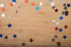 Konfettistjärnor på träbakgrund 4th Juli, självständighetsdagen, kortet, inbjudan i USA sjunker färger Sikten från överkant, tömm Arkivfoton