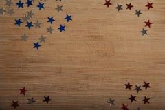 Konfettistjärnor på träbakgrund 4th Juli, självständighetsdagen, kortet, inbjudan i USA sjunker färger Sikten från överkant, tömm Arkivbilder